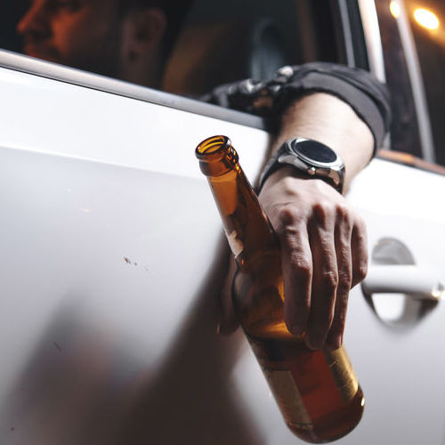 A Man Drives With a Beer in Hand.