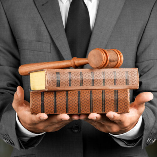 Suited man holding books and gavel.