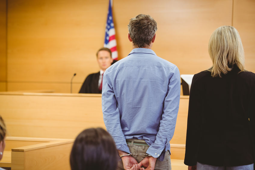 A Man Standing in Front of a Judge in a Courtroom.